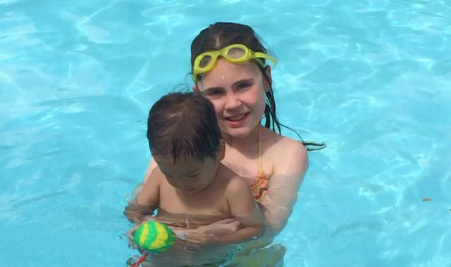 A girl helping a little boy to swim.