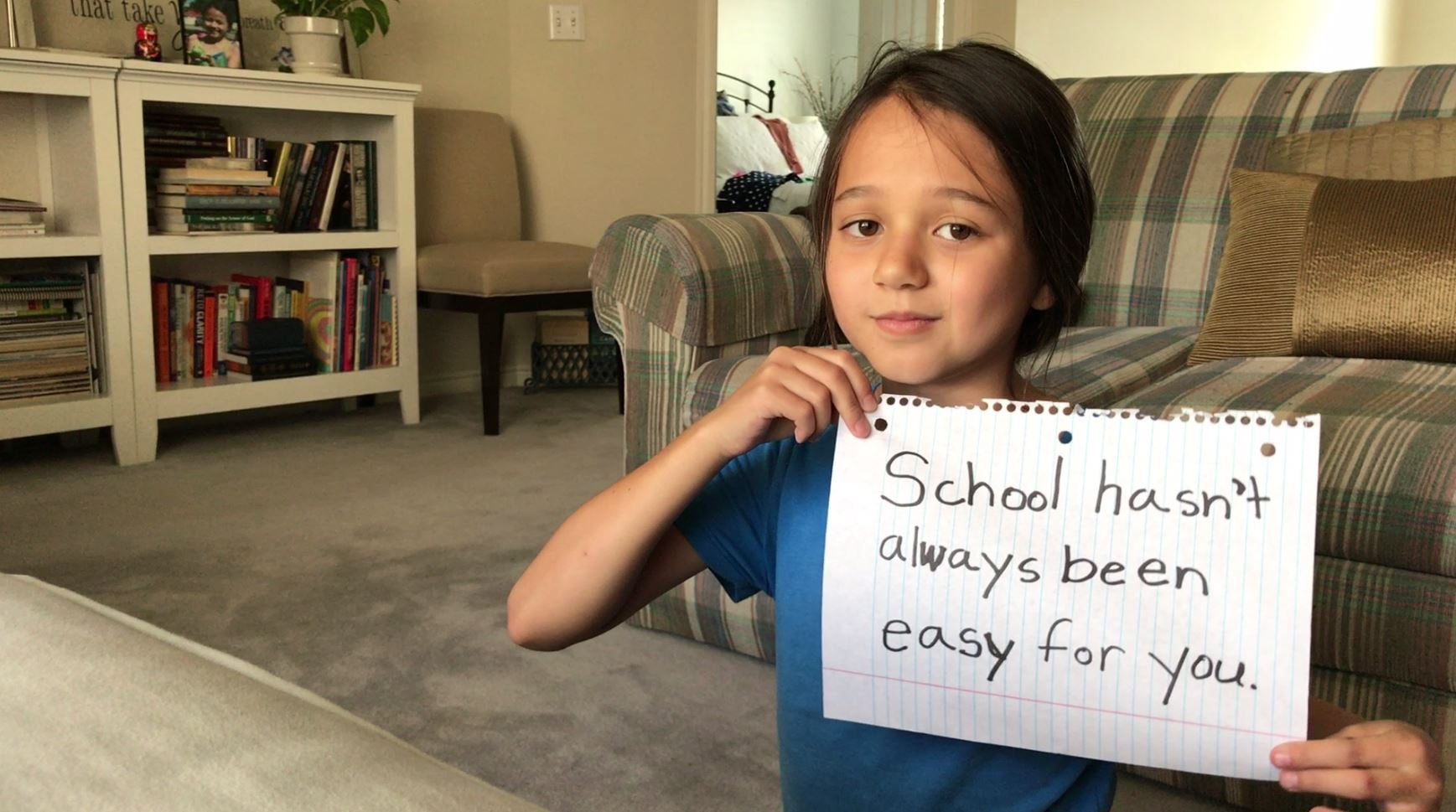 Young girl holds a motivational poster