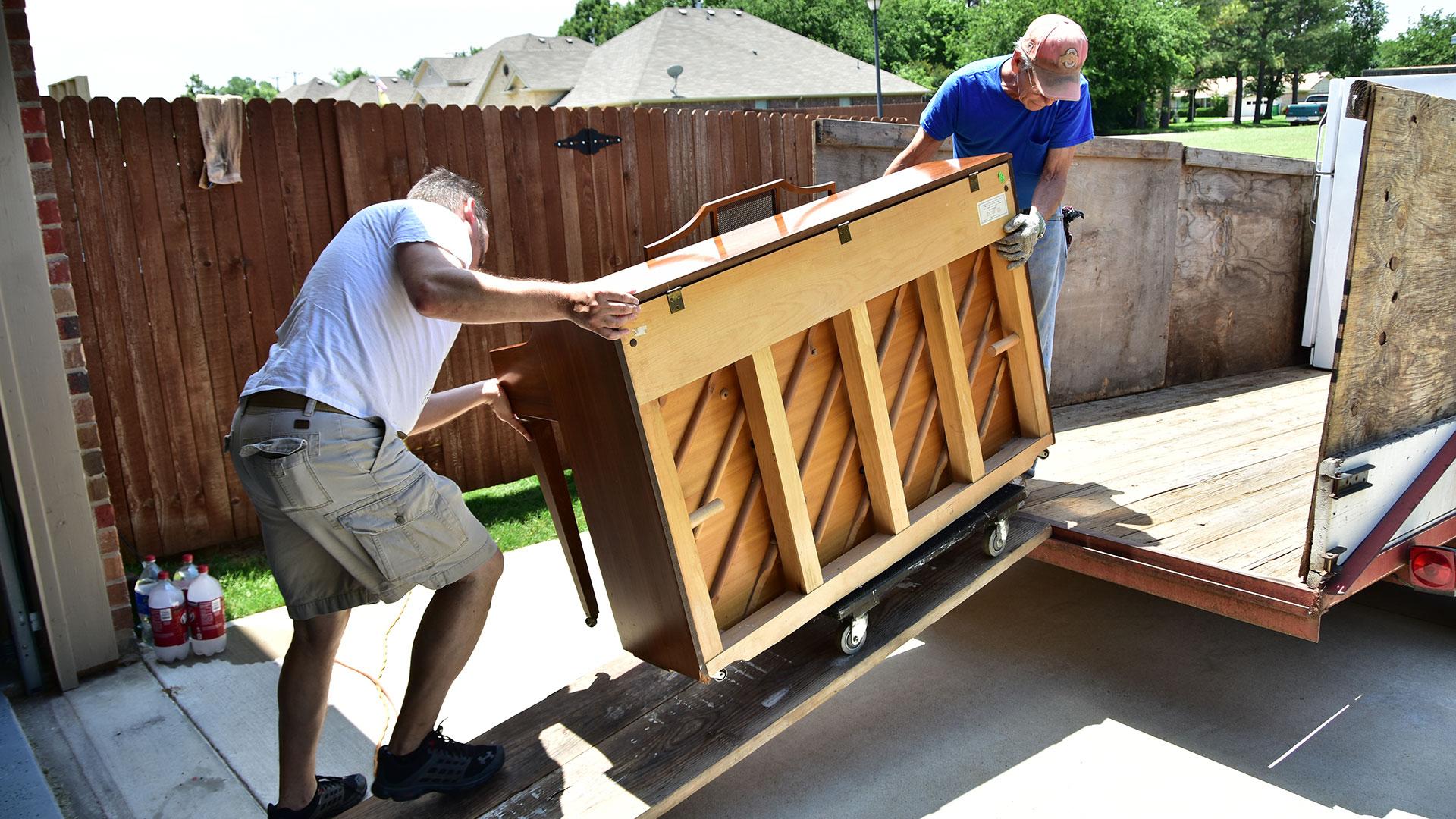 Two men pushing a piano up a ramp